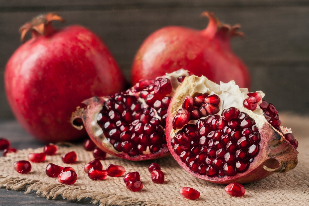 two pomegranate on the old wooden board with sackcloth
